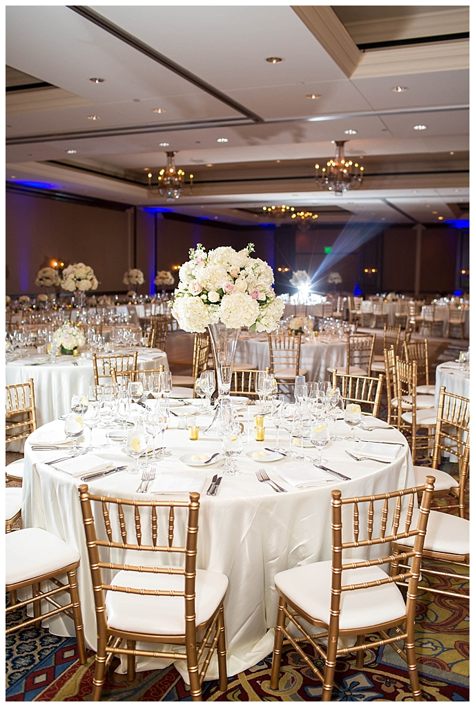 ballroom reception setup with gold chairs white large floral centerpieces at Omni Montelucia