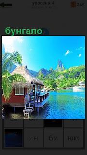 Стоит бунгало на озере с лестницей к воде и окнами, терраса сбоку