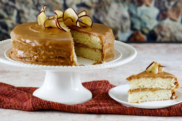 homemade southern caramel cake topped with apple chips on cake stand with slice nearby