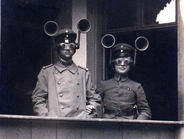 German sound location. The photograph shows a junior officer and an soldier from an unidentified Feldartillerie regiment wearing combined acoustic/optical locating apparatus. The small-aperture goggles were apparently set so that when the sound was located by turning the head, the aircraft would be visible. 1917.