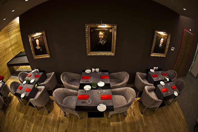Picture of square dining tables with grey velvet chairs by the dark brown wall