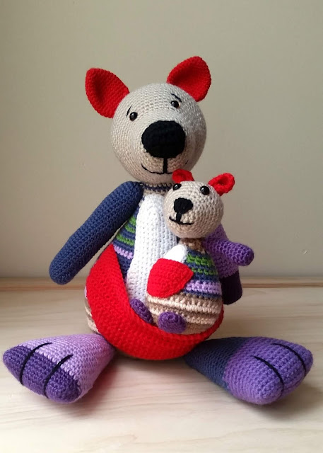 Front view of crocheted kangaroos. Joey is sitting in mother's red pouch.