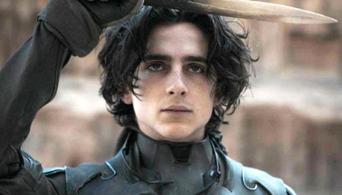 Imagem: o personagem Paul Atreides, interpretado por Timothée Chalamet, um garoto branco em roupas pretas com uma armadura escura, erguendo uma faca feita de um dente ou um osso afiado, ao fundo uma rocha desértica.