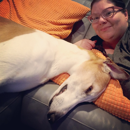 image of my face just peeking into the screen, wearing pink-framed specs, lying next to Dudley the Greyhound, who is taking up most of the frame