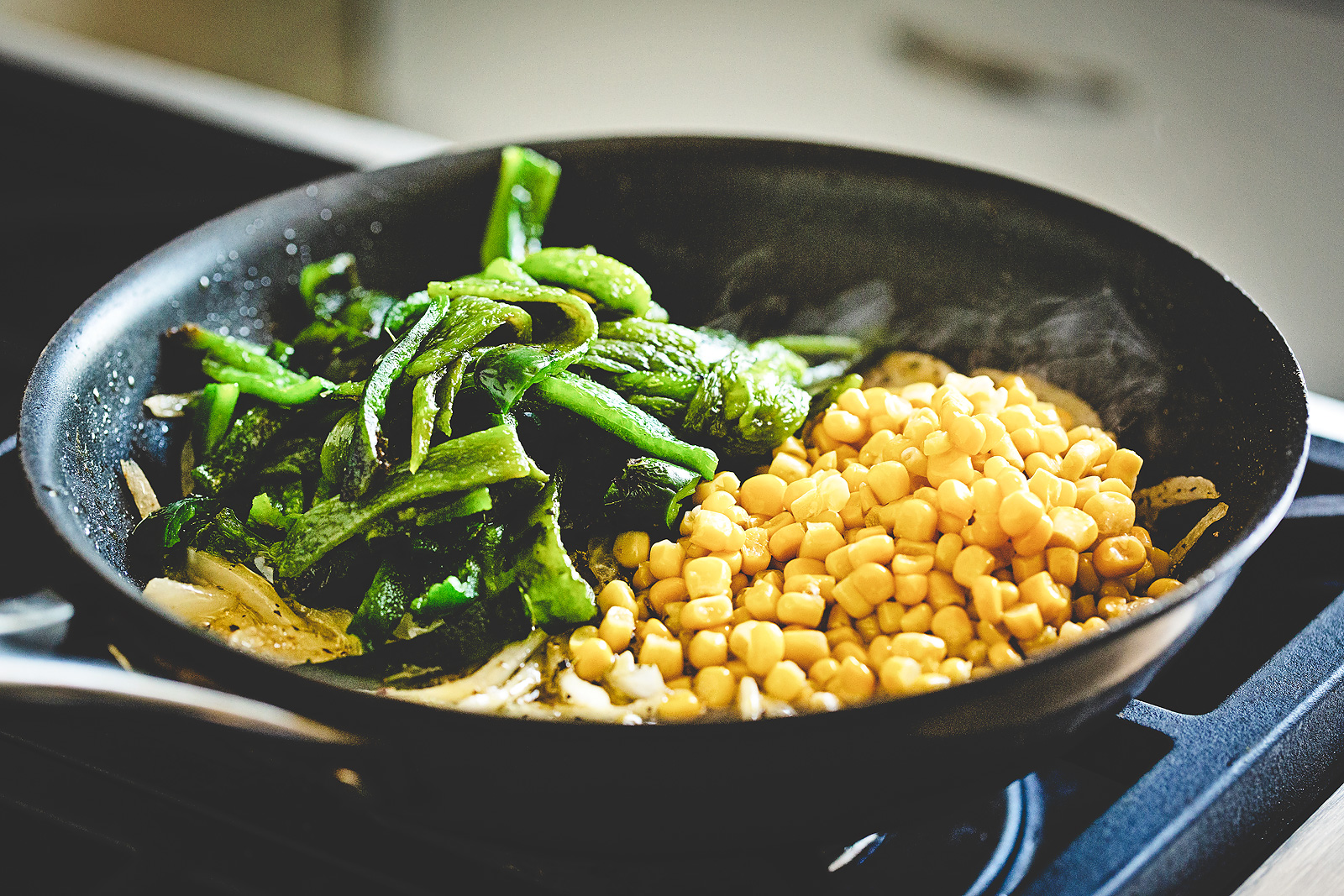 Roasted poblano strips and fresh corn kernels in a pan over onions.