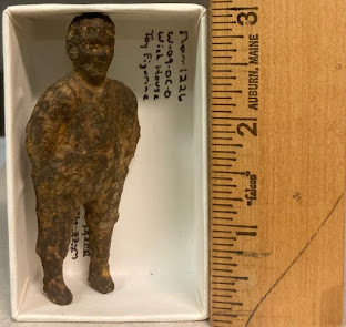 Small metal figurine in a box that has a ruler in inches to the right.