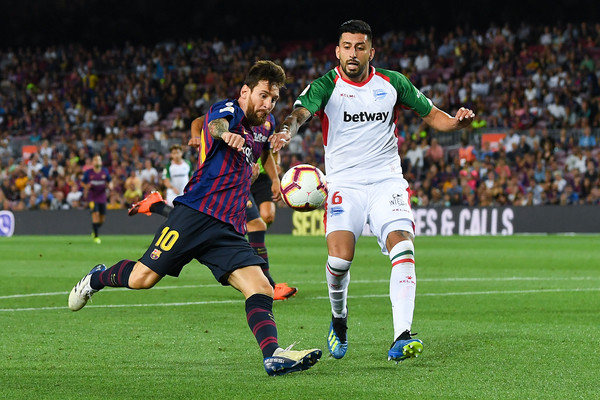 Lionel Messi of FC Barcelona shoots towards goal under a challenge by Guillermo Maripan of Deportivo Alaves during the La Liga match between FC Barcelona and Deportivo Alaves at Camp Nou on August 18, 2018 in Barcelona, Spain.