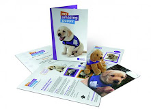 Information leaflets laid down. On top is a card with a picture of a puppy wearing a purple jacket and text reading 'My Amazing Puppy'.There is also a cuddly toy puppy wearing a purple Canine Partners assistance dog jacket, there is also a photograph of a puppy waring a purple jacket.