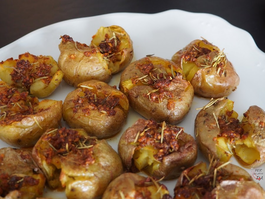 Patatas machacadas después de una primera cocción al vapor, y acabadas al horno con un aromático aliño mediterráneo.