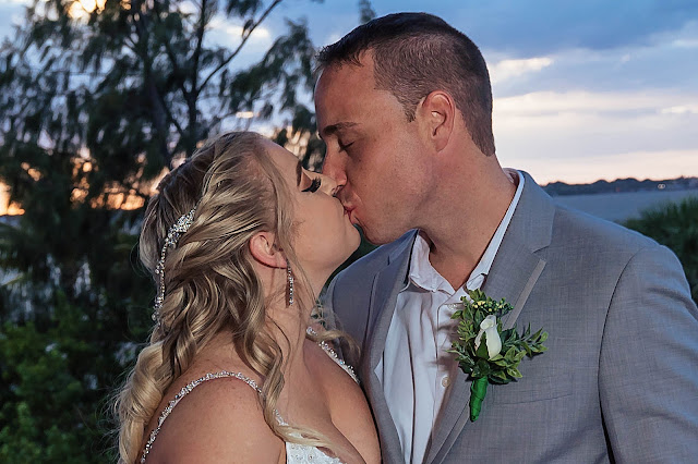 Bride and Groom kissing with the sunsetting
