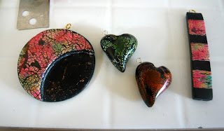 Swirled heart charms created from lentil beads, and two pendants using various scraps of inked clay