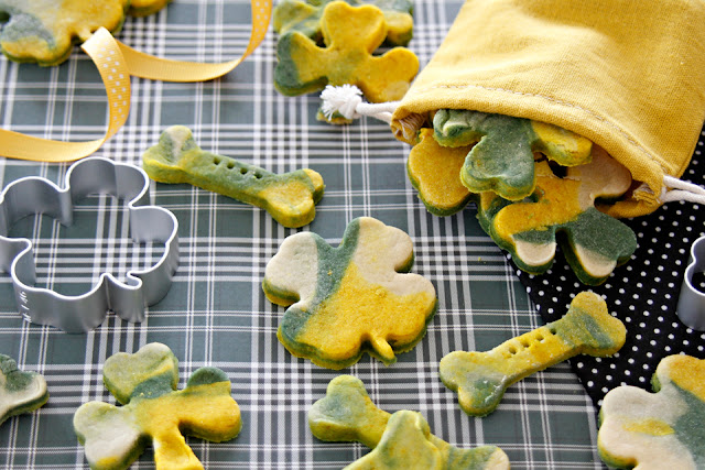 Homemade green and gold St. Patrick's Day dog treats shaped like shamrocks, clover, and bones