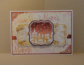 Christmas card in warm red and brown/cream shades; three squares with a central snow scene