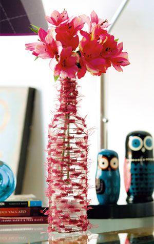 Garrafa de vidro trabalhada com um fio diferente se transforma em um lindo vaso que é uma peça de decoração bacana.