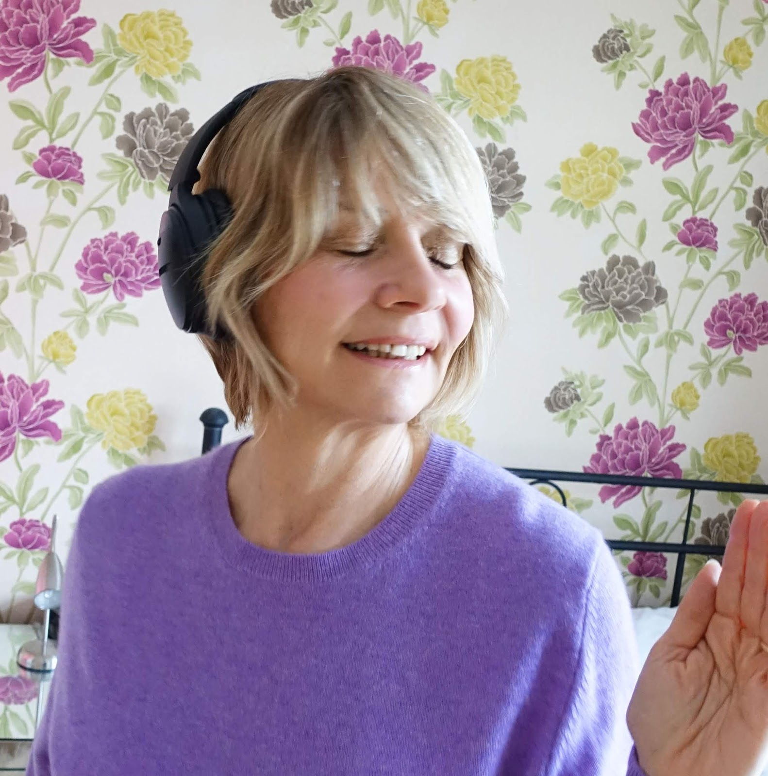 Over 50s woman listening to music with headphones on