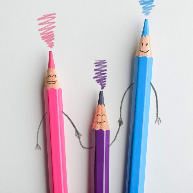 Pink, purple and blue crayon laid out with faces  drawn on to look like a family