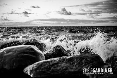 a monochromatic photo of waves at the shore of Georgian Bay hitting large rocks.