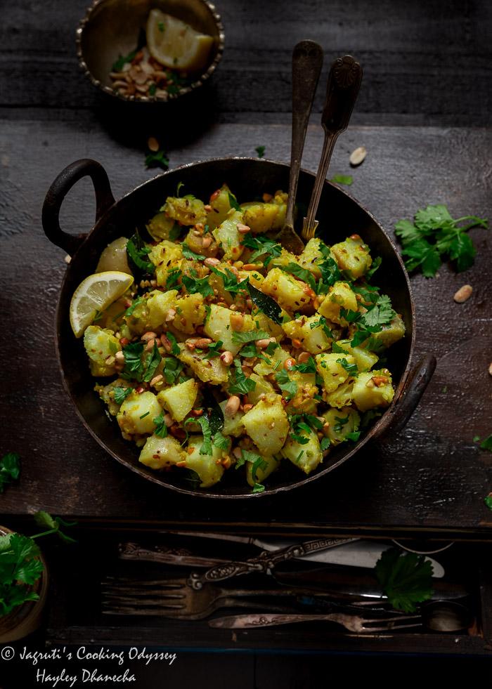 Vrat wale aloo peanut ki sabji in kadai topped with peanuts and coriander leaves with spoons