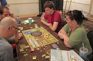 A group of four players sitting around the game board at a a   table, playing Tzolk'in: The Mayan Calendar