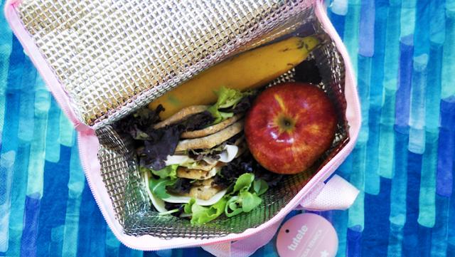 vista desde arriba la bolsa, abierta y su interior con manzana plátano y sándwiches