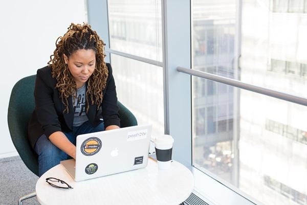 Girl Boss Mulher Negra sentada mexendo em notebook num ambiente clean
