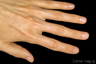 Photograph of a hand on a black background by Cramer Imaging
