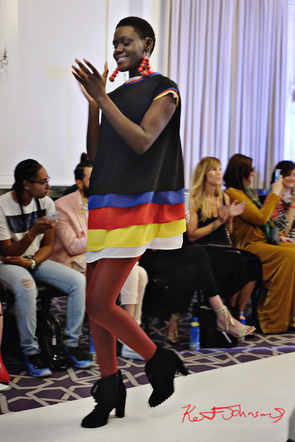 A model wears a black shift dress with ribbons of primary colour layering. André Bryson - Guerrilla - NYFW. Photographed for Street Fashion Sydney by Kent Johnson.