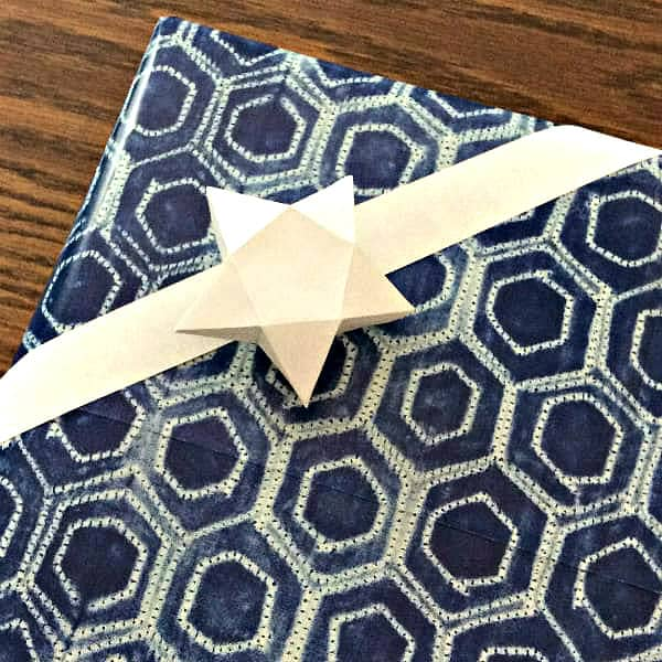folded paper star as bow on gift wrapped in shibori patterned paper