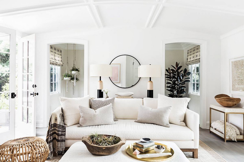 A rustic and white living room with natural, organic, and boho chic design features a linen sofa, and natural woven accents. It is Erin Fetherston's California modern farmhouse with its white walls and breezy clean style. #whitelinen #livingroom #rusticdecor #beachy
