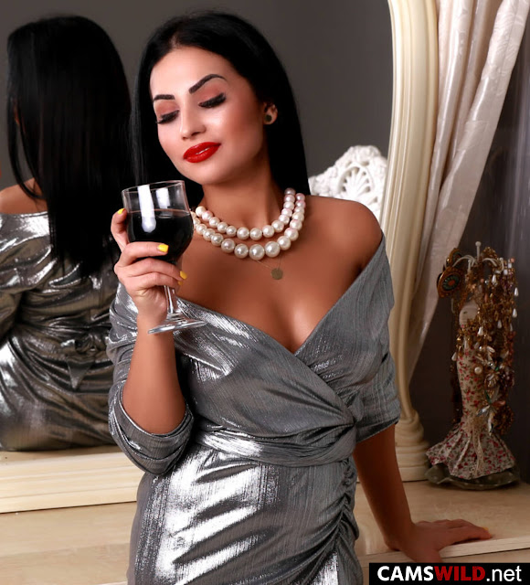 camswild-heiditaylor-black-hair-woman-in-silver-dress-drinking-red-wine