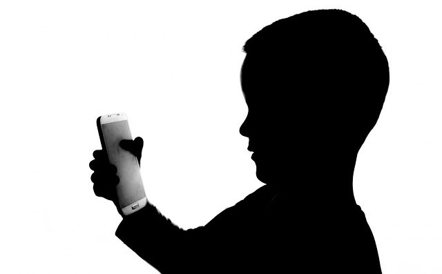 Silhouette of a child holding a smartphone