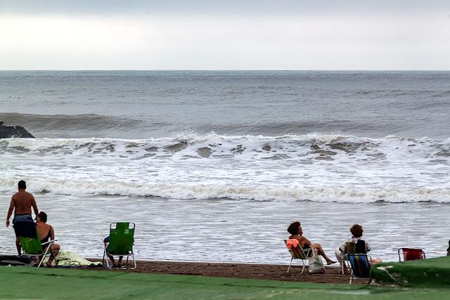 En mar llegando a la playa y gente descansando en sus reposeras.