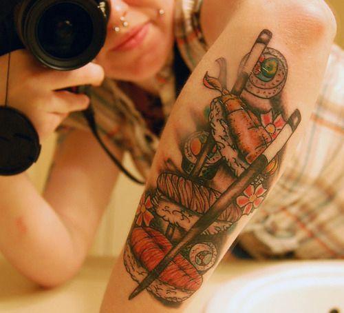 Chica acostada sacando foto de su antebrazo en el que luce un tatuaje de sushi