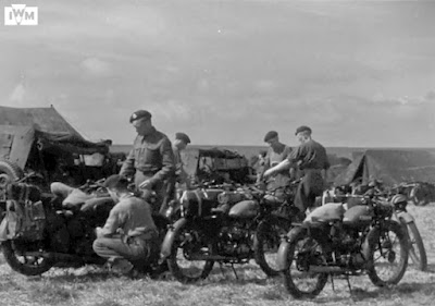 Soldiers prepare motorcycles to be packed for airborne invasion.