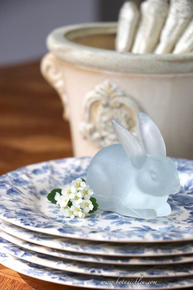 A sweet blue bunny sits on top of a stack of blue floral dishes for an easy Easter tablescape