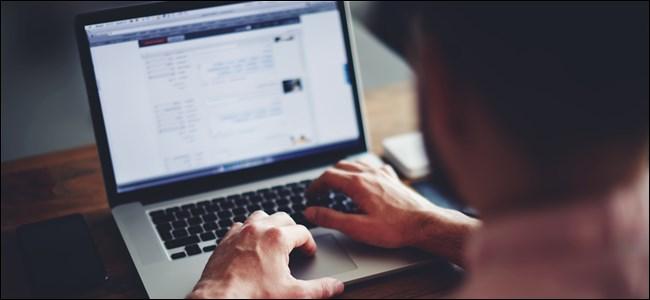 كتابة الرجل على لوحة مفاتيح الكمبيوتر المحمول.
