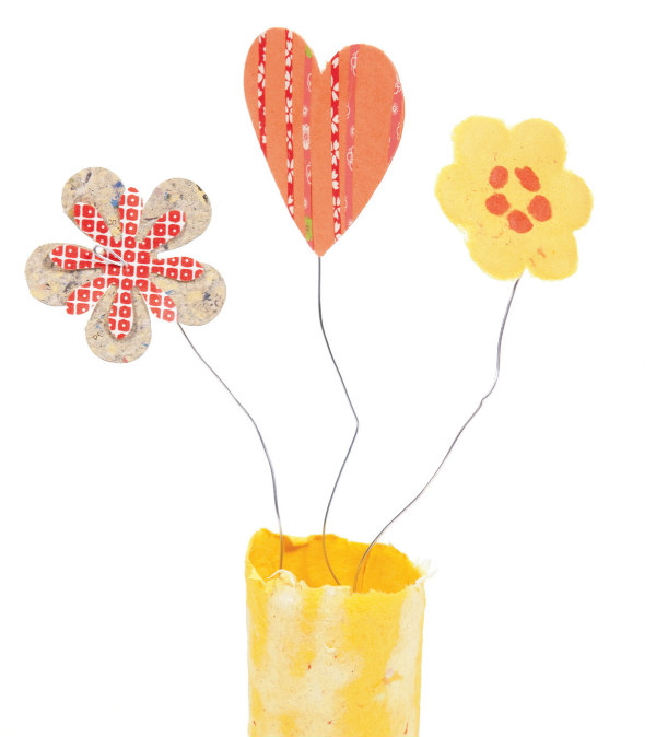 three recycled paper flowers in a paper vase