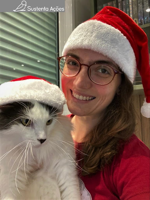 Letícia segurando o gato Spock, os dois com toquinha de Papai Noel