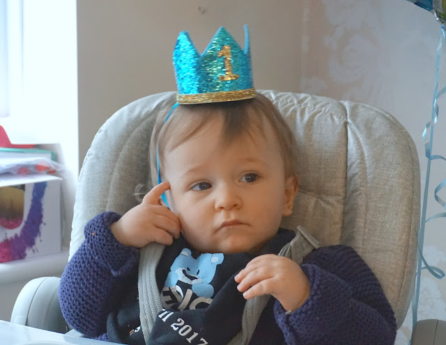baby boy wearing birthday crown and looking thoughtful