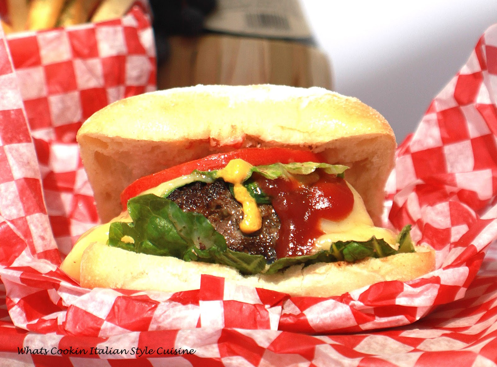 this is an Italian seasoned beef burger in a ciabatta bread roll pillow soft hamburger better than any fast food burger. This burger has lettuce tomato condiments, cheeses, and bursting with the best Italian flavors.