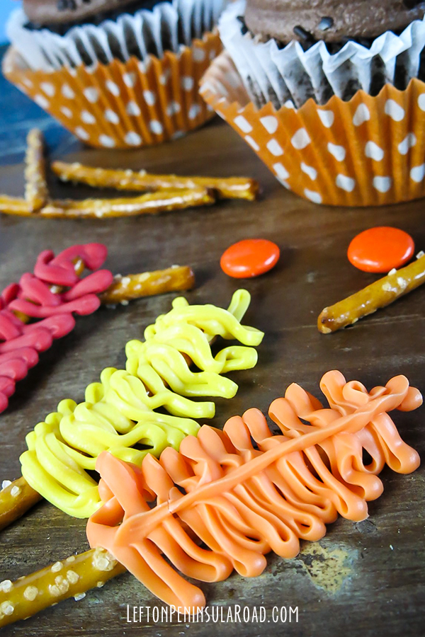 Pipe candy-coating on pretzels to make feathers for Turkey cupcakes.