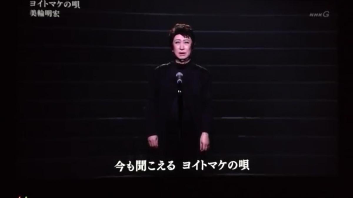 暗闇の中で男装して『ヨイトマケの唄』を歌う美輪明宏
