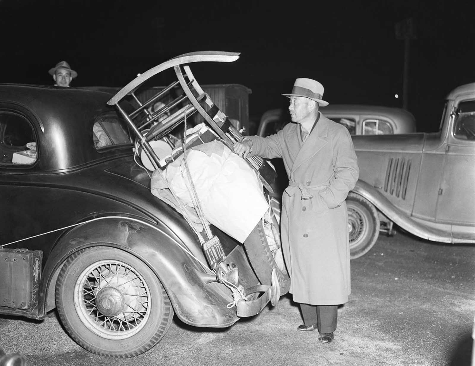 A man in Pasadena packs his car with belongings before heading to the Manzanar War Relocation Camp.