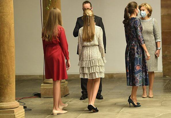 Queen Letizia wore a dress by Carolina Herrera. Crown Princess Leonor wore a print dress by Poeta. Infanta Sofia wore a red shirt dress by Mango