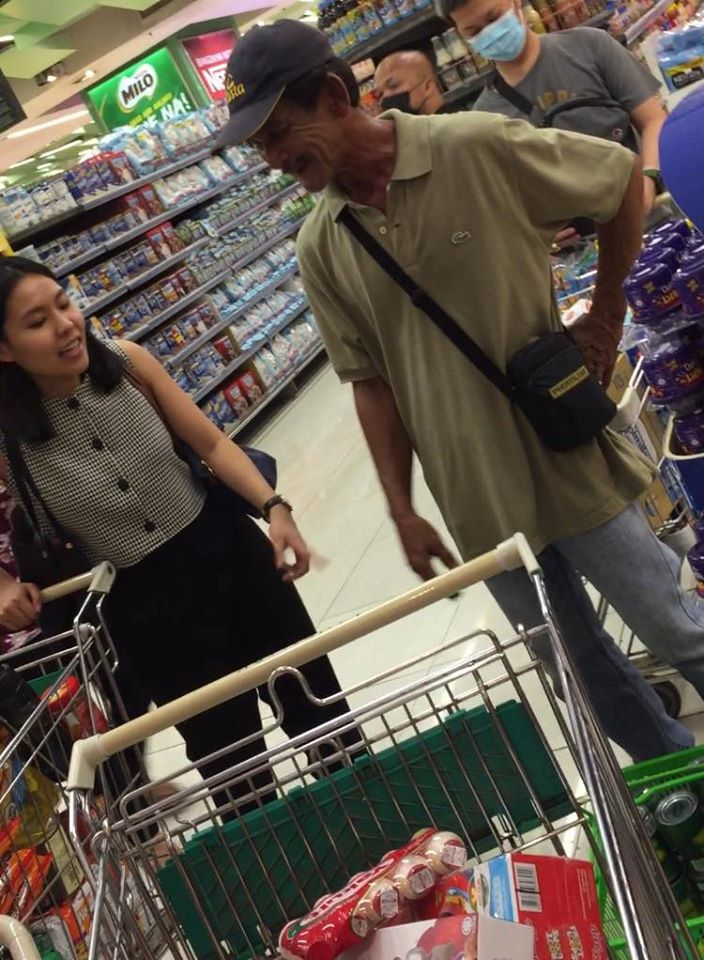 Kind woman buys groceries for old man with only few canned goods in basket