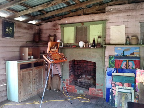 Photograph of a slightly dilapidated room set up as an art studio and featuring a pochade box on a tripod and a fireplace.