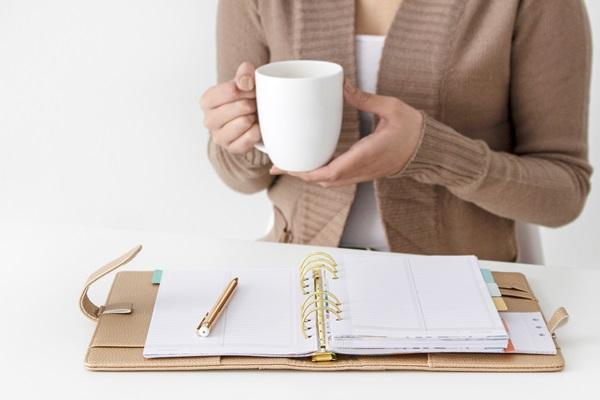 Mãos femininas segurando uma caneca branca nas mãos à mesa com um fichário em cima