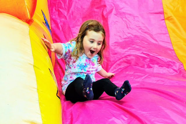 Image of a young girl wearing a tie dye t shirt and black leggings sliding down a bright pink and yellow inflatable slide.