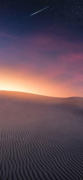 خلفية بزوغ الفجر على رمال الصحراء الشاسعة