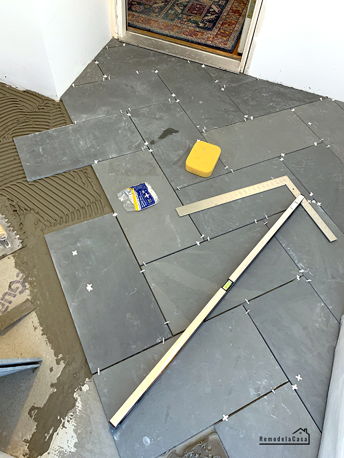 Slate tile being installed in a herringbone pattern